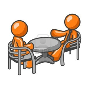 1905758-two-orange-business-men-sitting-at-a-table-having-a-business-conference-or-maybe-its-just-two-friend